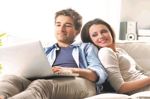 Man on laptop and woman leaning back - Educators Financial Group