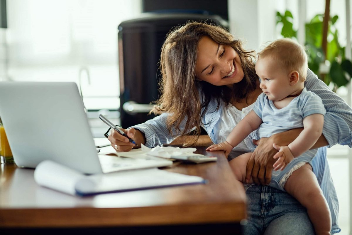 mother-holding-baby-calculating-finances-budget