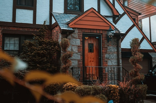 House with fall leaves - Educators home buying in the fall