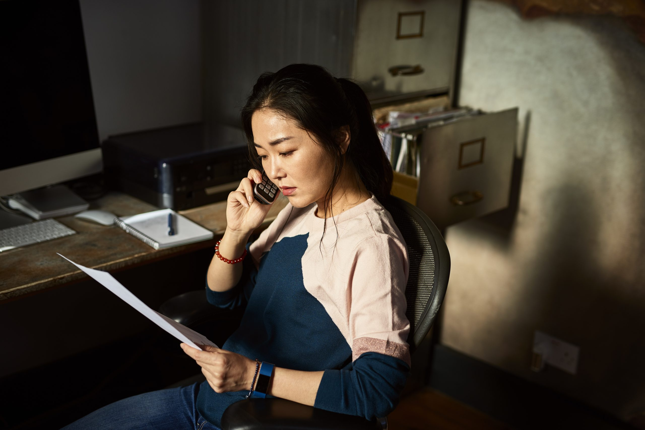 Portrait of Asian woman on cell phone reading important document