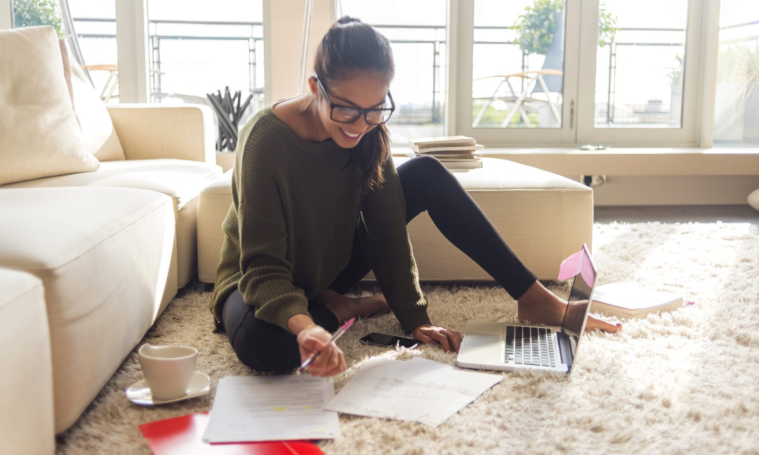 smiling young woman working on laptop in her living room
