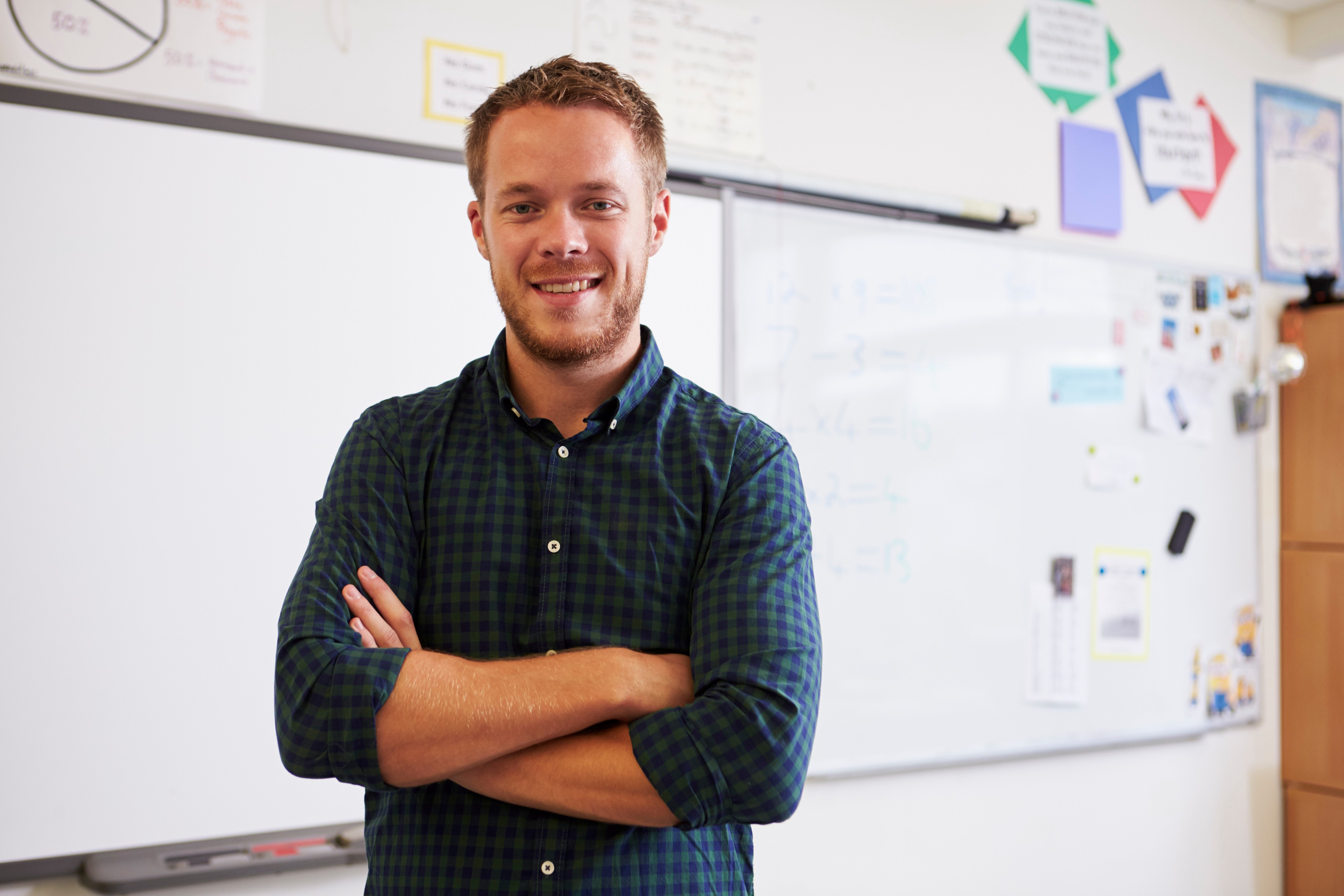 young-male-teacher-standing-in-classroom