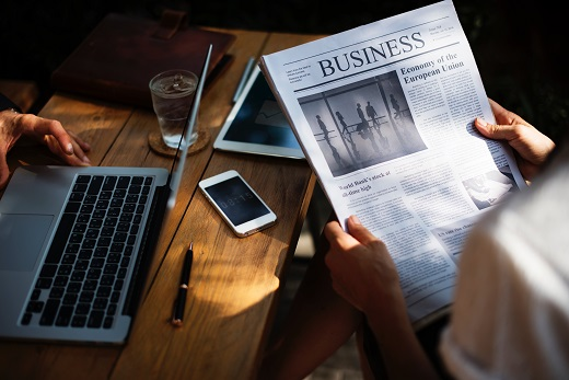 Business newspaper and laptop - Educators Financial Group
