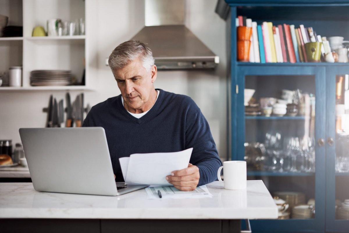 man sitting in front of computer reviewing finances