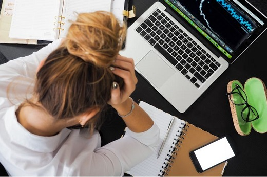 Woman holding head with graph on laptop - Educators Financial Group