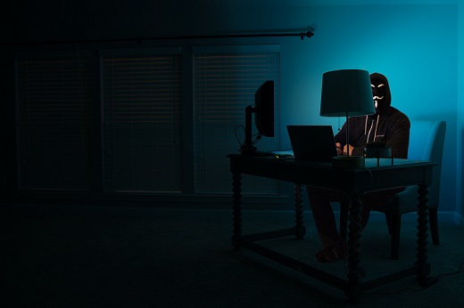 Man sitting facing laptop in dark room