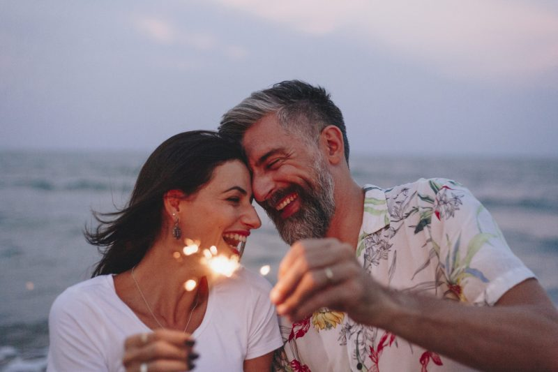 couple celebrating early retirement with sparklers at the beach