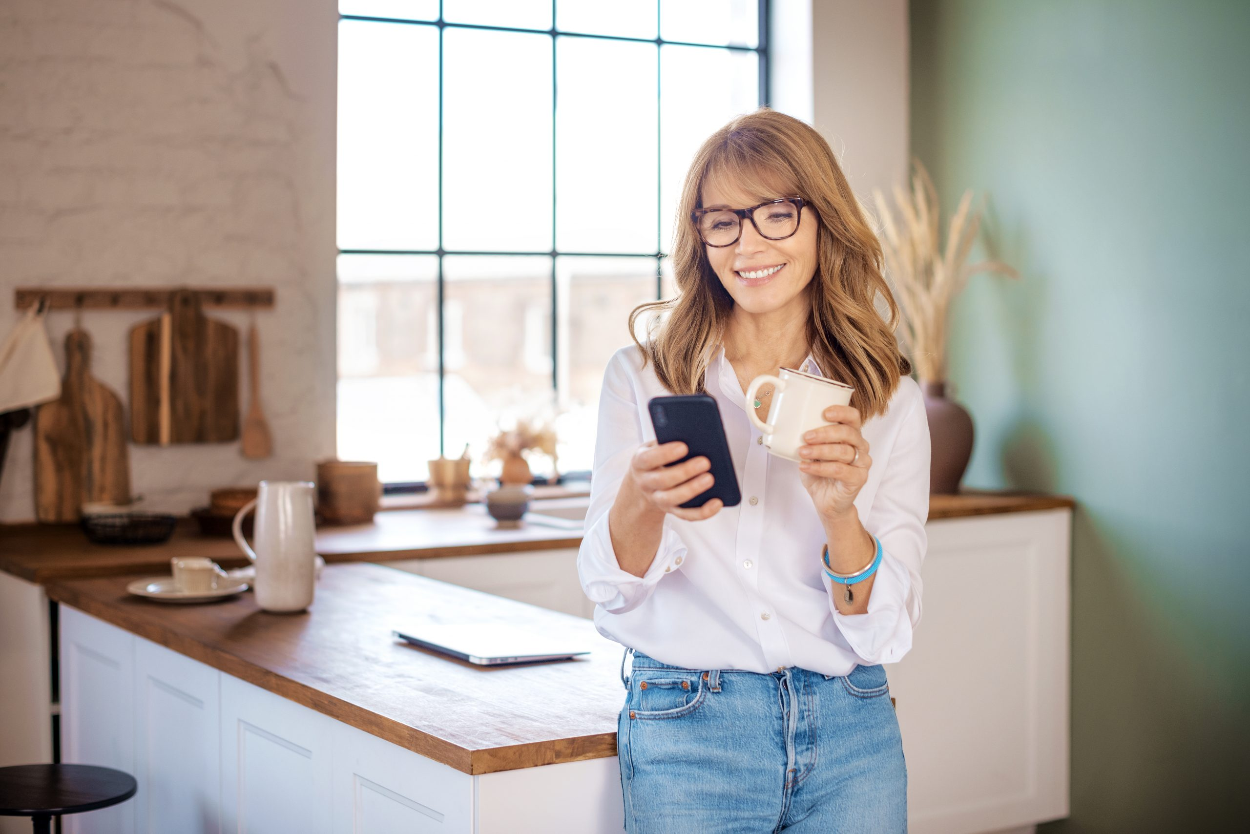Smiling woman looking at cellphone and drinking coffee while standing at her kitchen in the morning