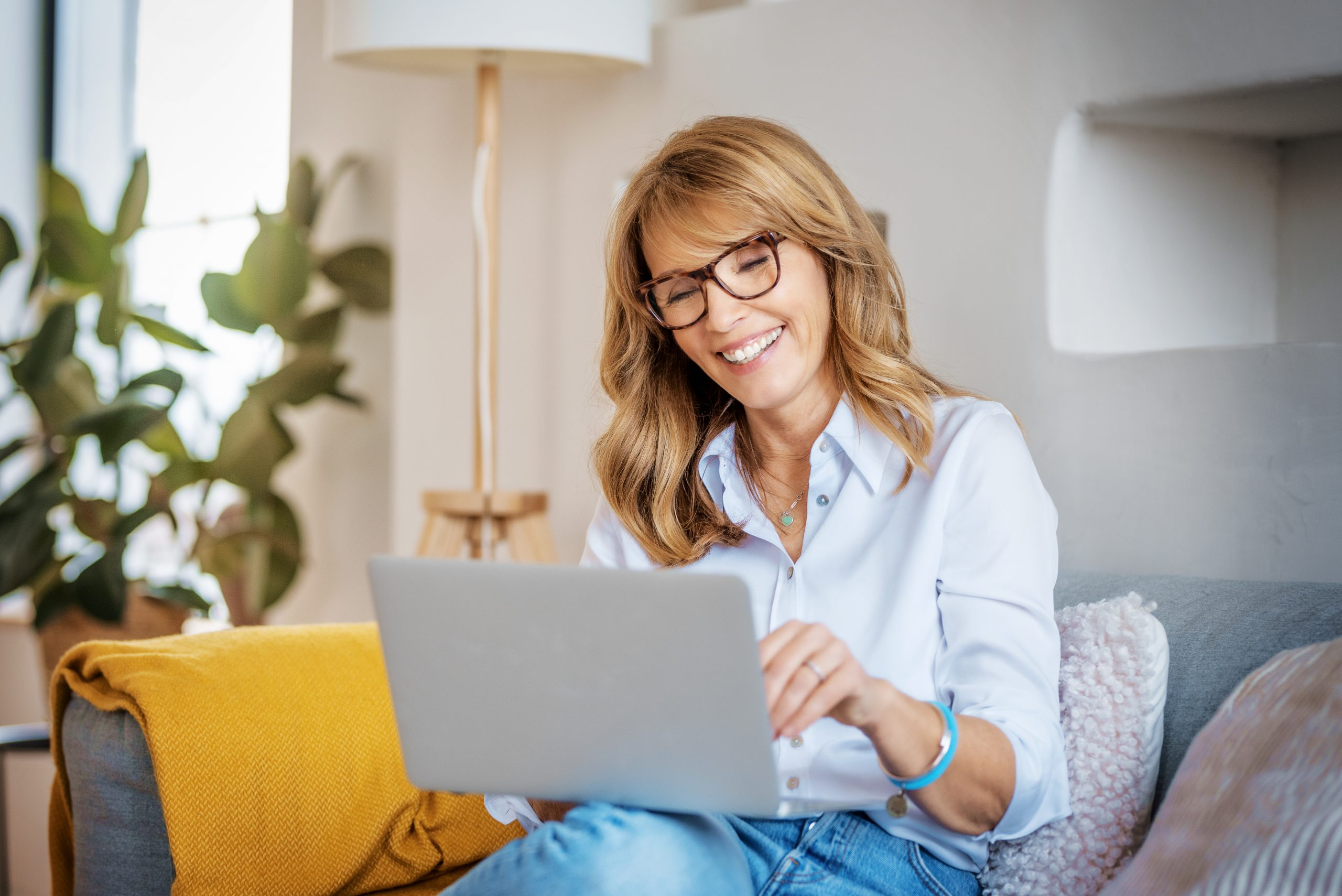 Happy woman using laptop while sitting on the couch at home