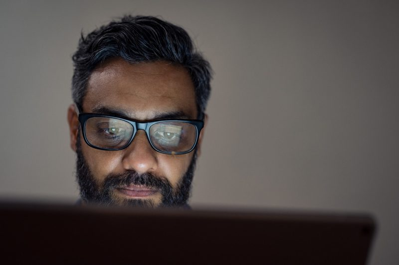 Mature man wearing eyeglasses sitting and using laptop in a dark office.