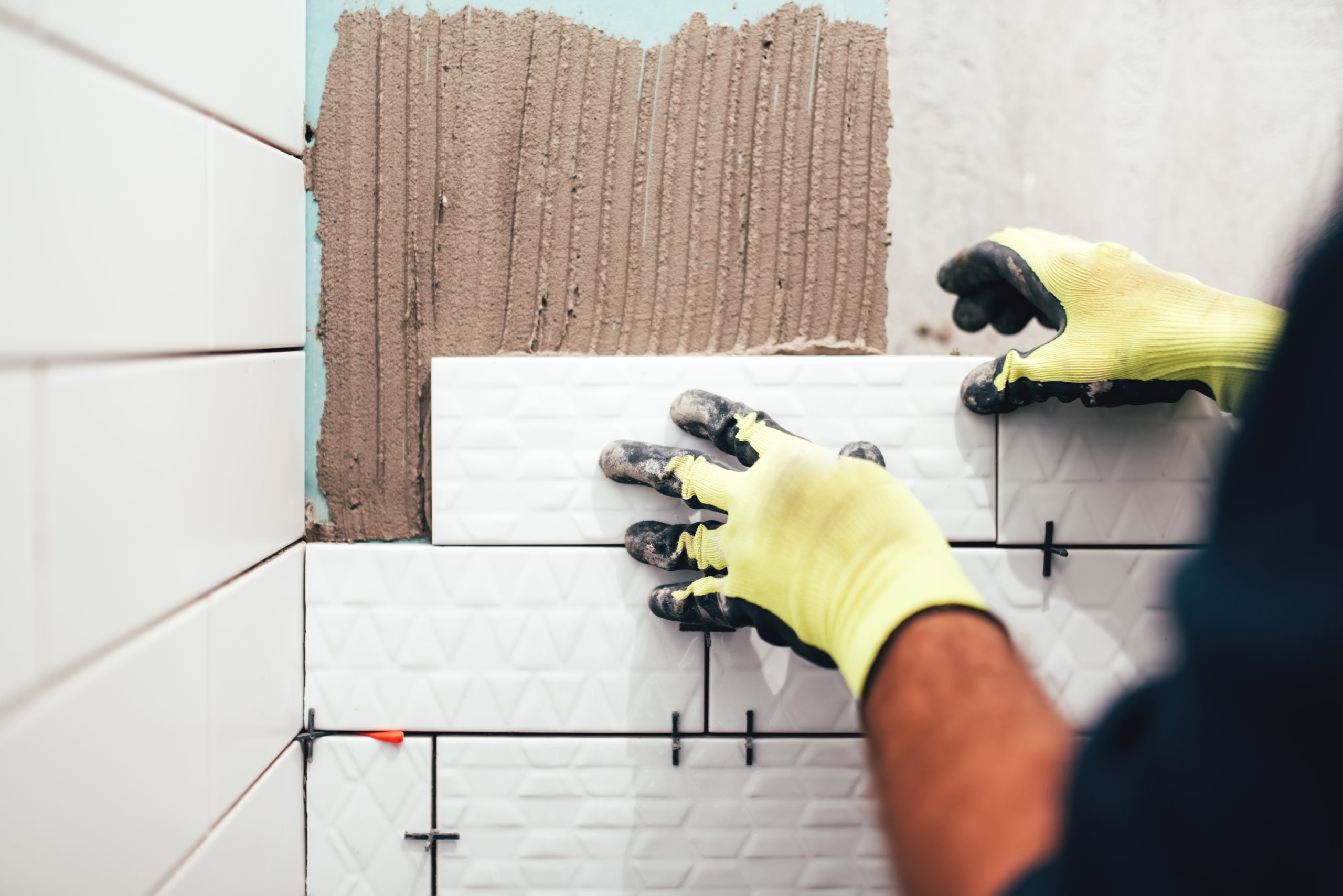 industrial construction worker installing small ceramic tiles on bathroom